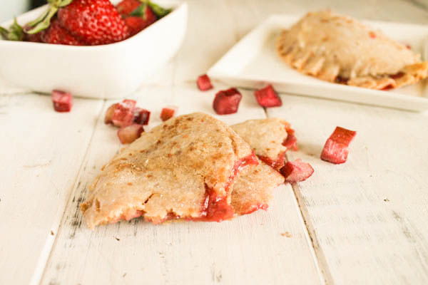 a torn strawberry rhubarb hand pie with the filling oozing out and scattered fresh diced rhubarb