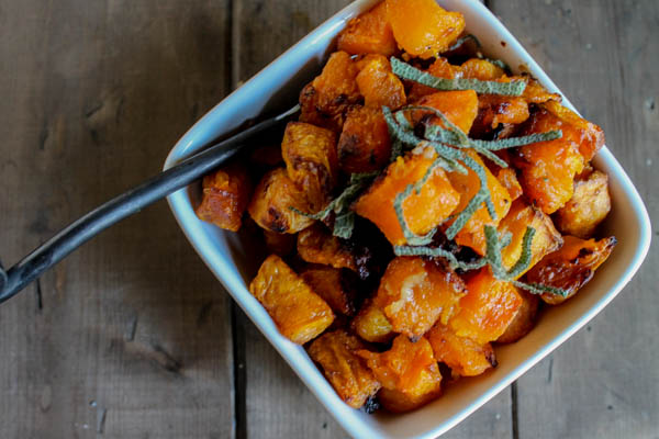 overhead shot of whole30 roasted butternut squash in a white square bowl on a dark wooden surface