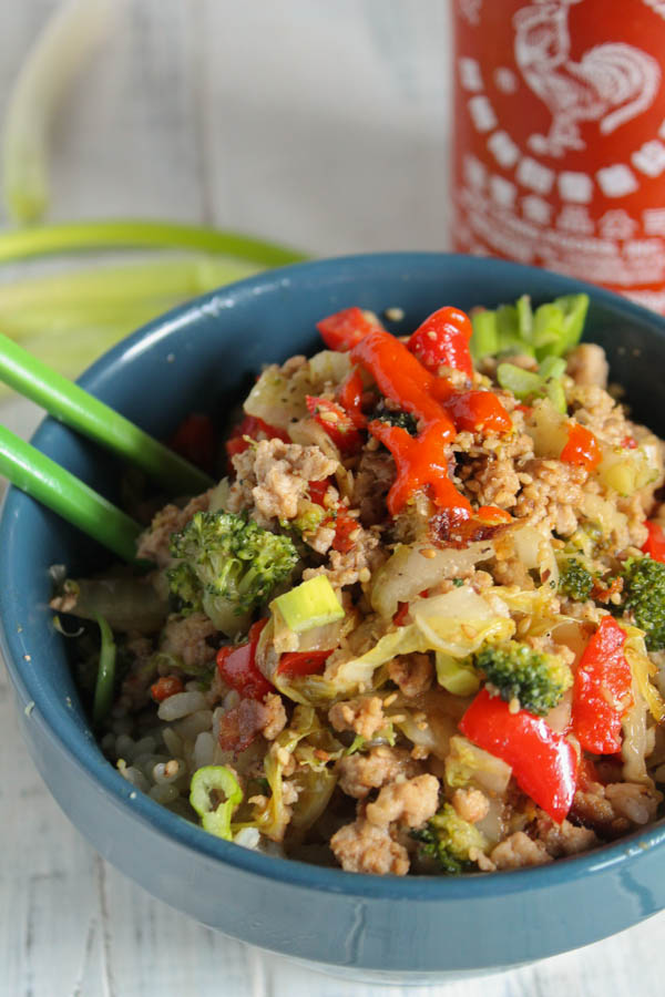 vertical image of a dusty blue bowl filled with ground meat with broccoli and red peppers