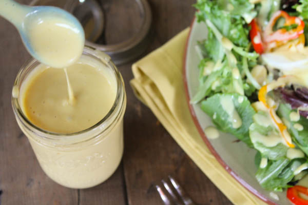 horizontal image of paleo honey mustard dressing in a mason jar drizzling off a blue spoon