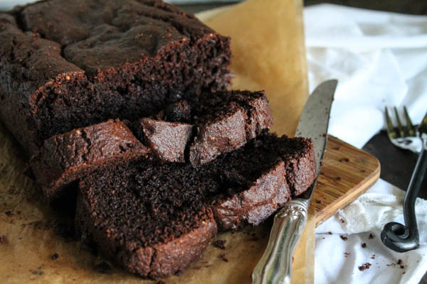 close up of sliced chocolate zucchini bread on a brown parchment and a silver knife