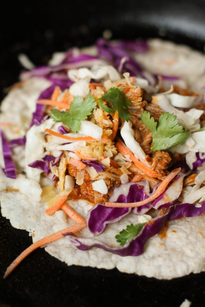 vertical close up of chicken tings taco topped with vibrant multi colored slaw