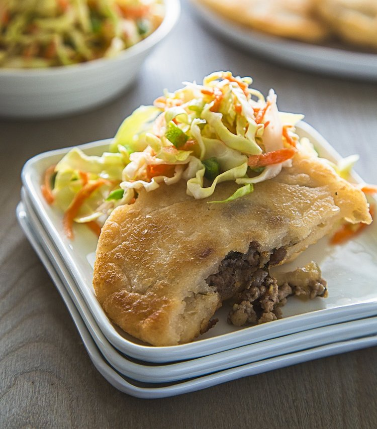 a meat filled pastry topped with a fresh cabbage slaw on white plate