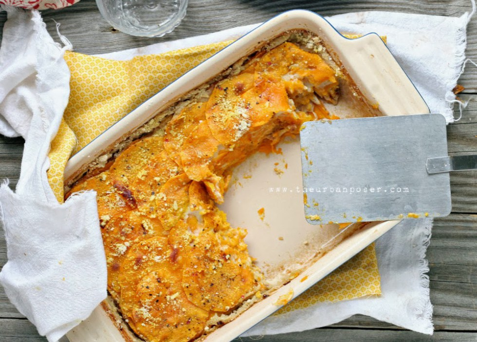 overhead shot of a pan of thinly sliced butternut squash layered with a creamy sauce ad rustic serving spatula
