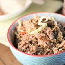 horizonatal image of tender pulled pork in a turquosie and red lined bowl on a dark wooden surface