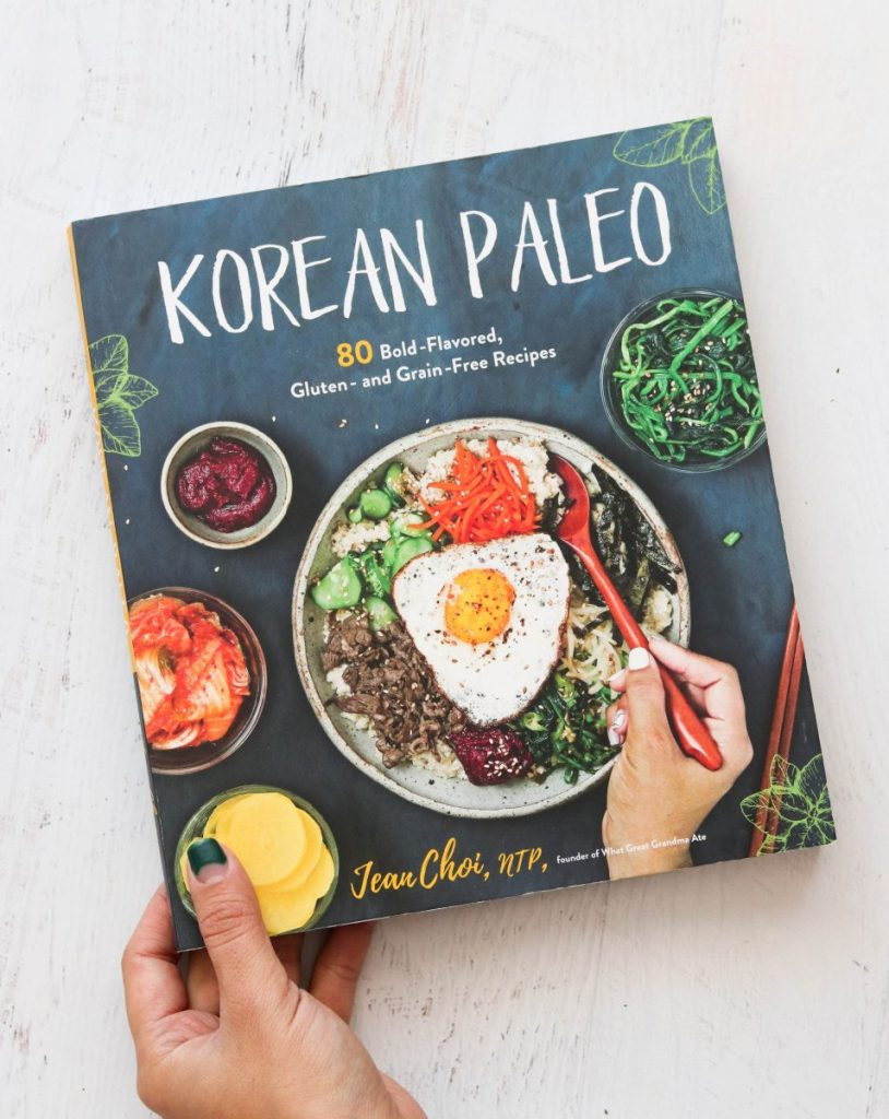 vertical image of korean paleo cookbook from overhead on a light surface with a hand holding the book in the left hand corner