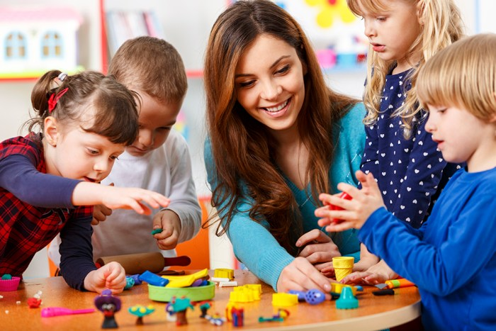 Teacher playing with students. Toys are scattered on the table.