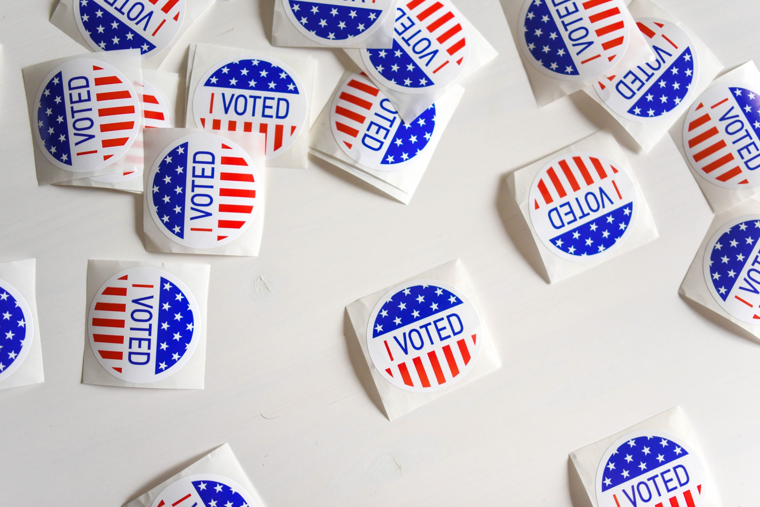 """""""I Voted"""" stickers scattered on a white table."""