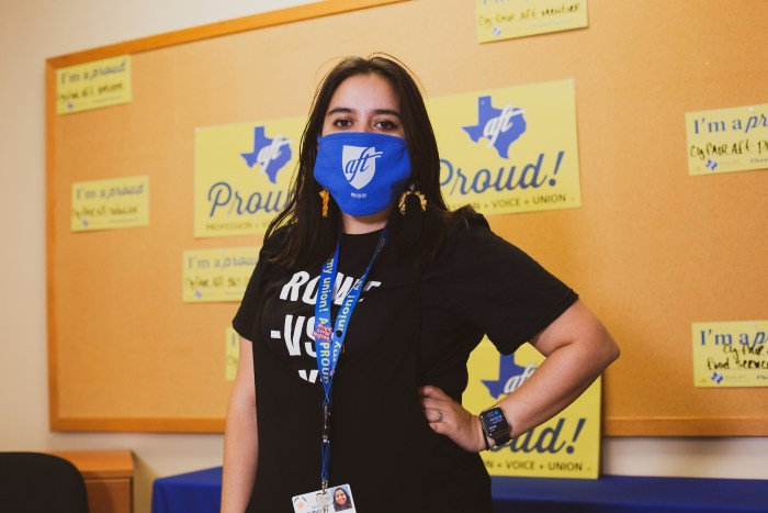 """Mariah Najmuddin poses with hand on hip and an A-F-T face mask in front of a corkboard with yellow """"Texas A-F-T Proud"""" signs."""