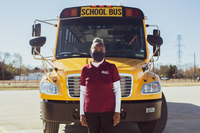 Linda Barrett stands in front of a school bus wearing a face mask and her driver's uniform.