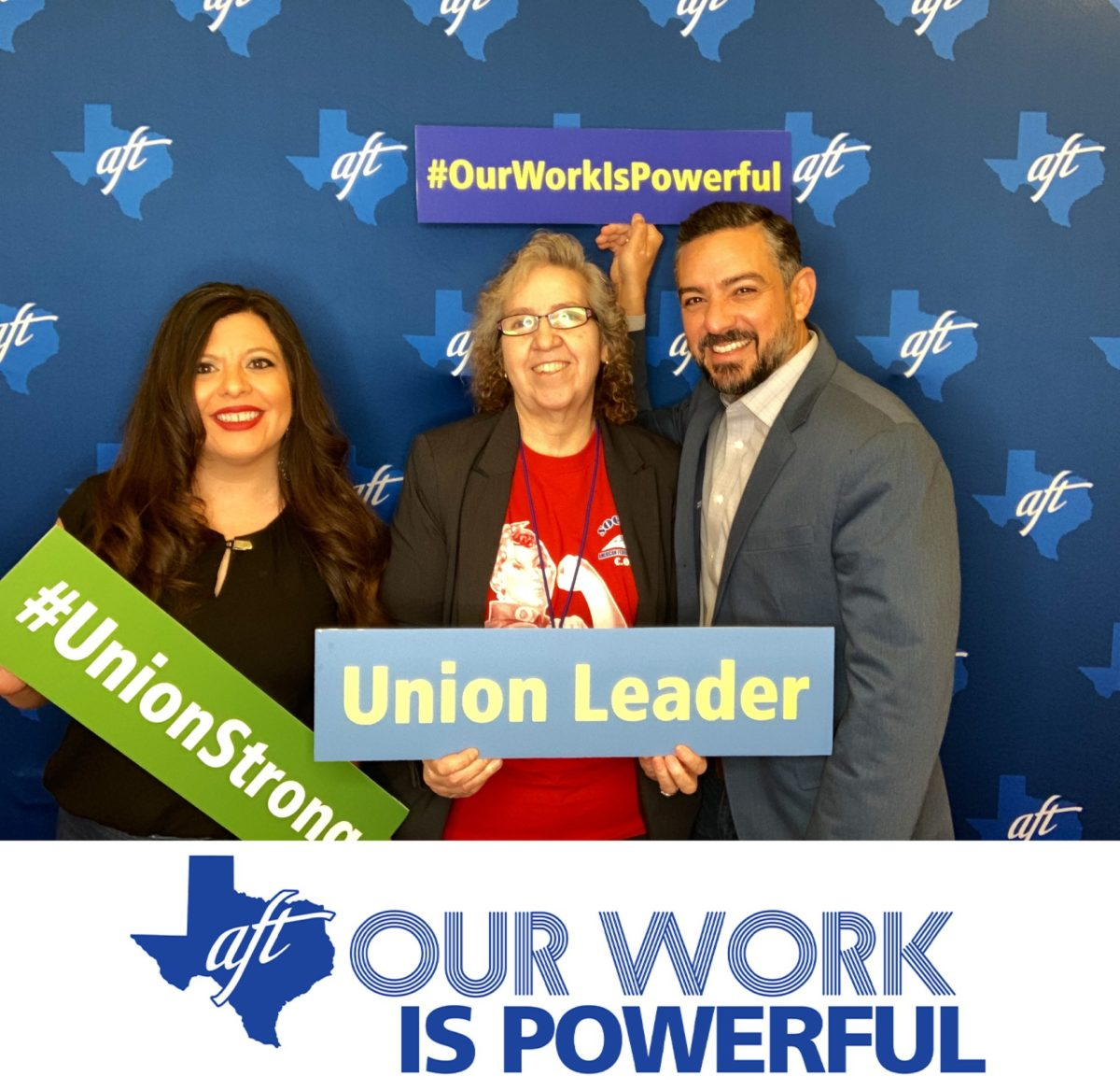 """Veronica Hernandez, Representative Mary Gonzalez, and Senator Cesar Blanco pose for a photo with signs that say """"Union Leader,"""" """"Hashtag Union Strong,"""" and """"Hashtag Our Work Is Powerful."""""""