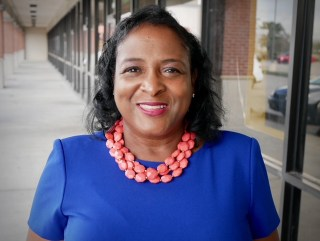 Photo of Shonda Below outside an office building. She is wearing a blue top and a coral, multi-stringed necklace.