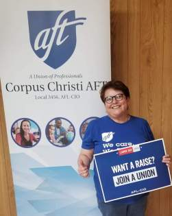 """Nancy Vera stands in front of a Corpus Christi banner. She is holding a sign that reads, """"Want a raise? Join a union."""""""