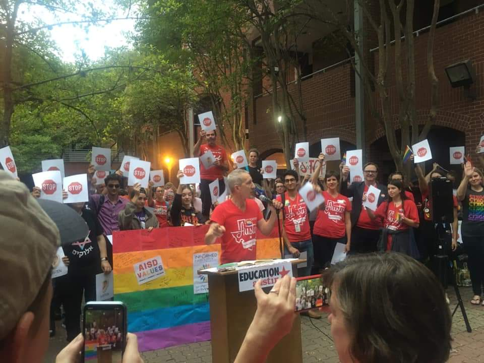 """Ken Zarifis speaking at an outdoor Education Austin rally. Behind him are members holding """"Stop"""" signs."""