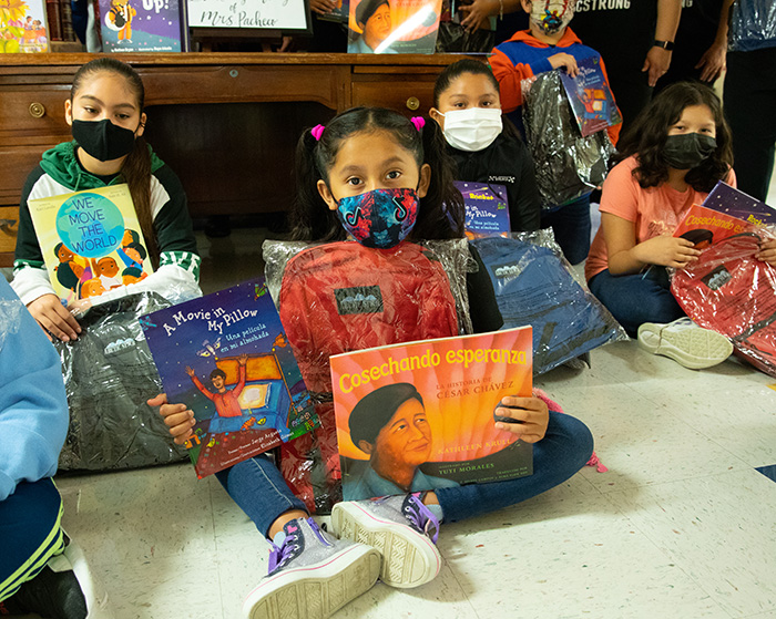 Four students sit on the floor, masked, displaying their new books they received