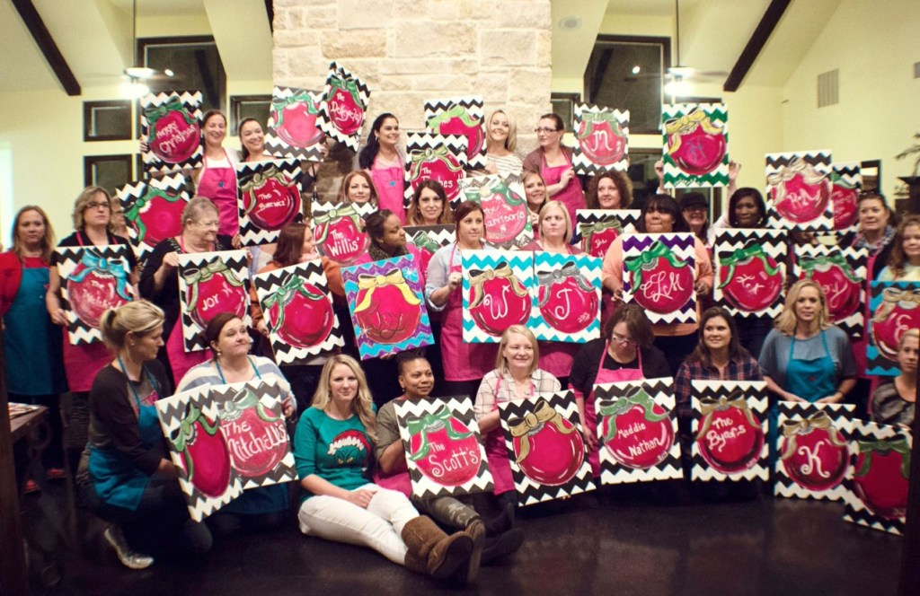 huge group of women holding finished canvases at a paint party