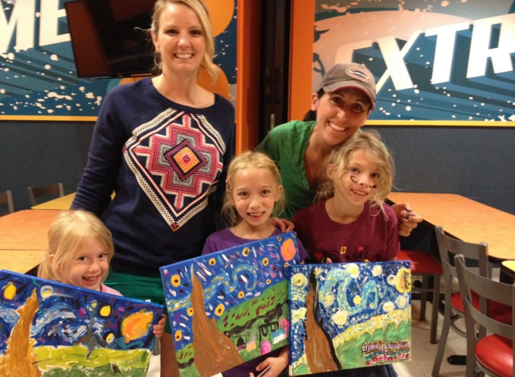 kids at a paint party holding finished canvases