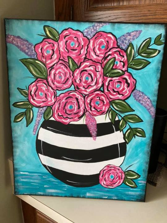 painting pink flowers in a black and white vase
