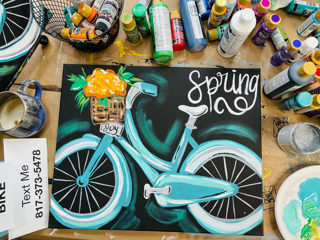 acrylic painting of blue bike with basket of flowers on table with paint bottles