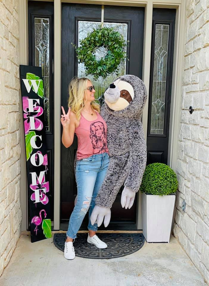 woman standing near a welcome flamingo sign holding a giant stuffed sloth