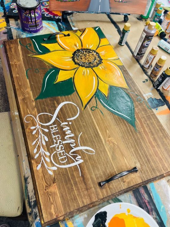 """noodle board with hand painted sunflower and stenciled words """"simply blessed"""" and bottles of acrylic paint"""