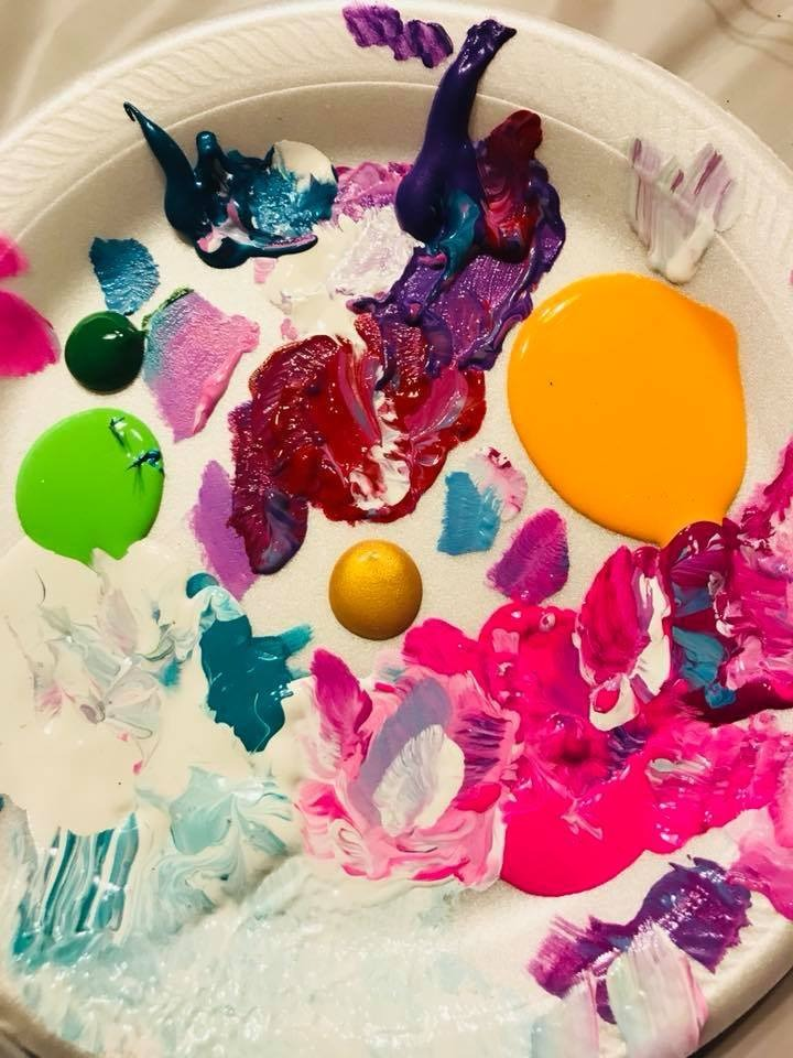 Paper plate filled with colorful paints