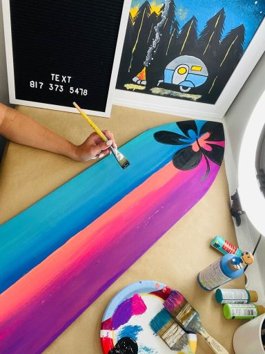 colorful decorative surfboard and acrylic painting with camper in the woods