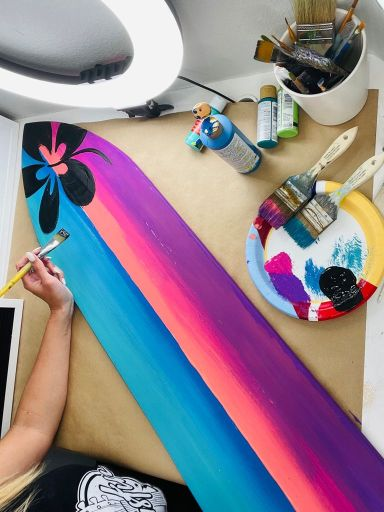 colorful decorative surfboard with hibiscus and art supplies