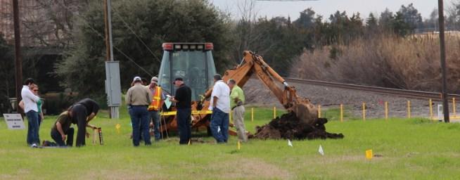 Backhoe at damage site - Investigators marking site