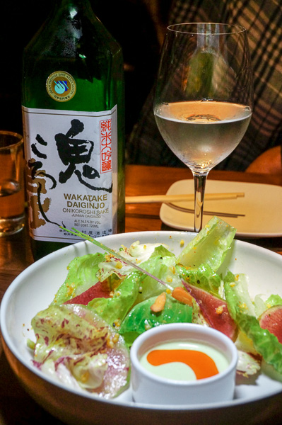 Uchi Salad with farm greens and edamame-jalapeño dressing, accompanied by a lovely glass of sake.