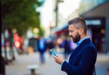 Hipster manager holding smartphone, texting outside in the street