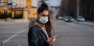 Girl in protective mask using smartphone outdoors. COVID 19. World coronavirus pandemic