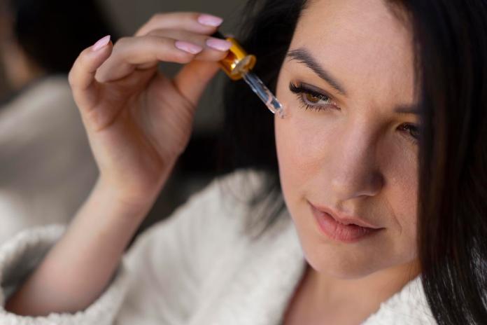 Mujer aplicando productos para disfrutar de los beneficios del ácido hialurónico