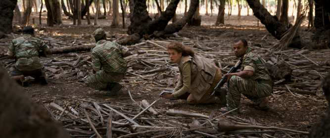 Marie Colvin (Rosamund Pike) quietly treads on dangerous ground with her notebook in hand in A PRIVATE WAR.