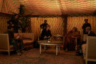Paul Conroy (Jamie Dornan) photographs Marie Colvin's (Rosamund Pike) interview with Libyan leader Colonel Muammar Gaddafi (Raad Rawi) in A PRIVATE WAR.