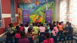 Children listen attentively to Thelma Perkins at Tobago's Bocas Lit Storytelling Caravan.