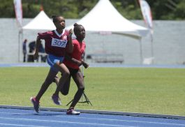 Kevah Scott of St Andrew's Anglican Primary school overtakes Jelissia Alexander of Scarborough RC on the final lap of the first 1500m Open race. Scott went on to win the event.