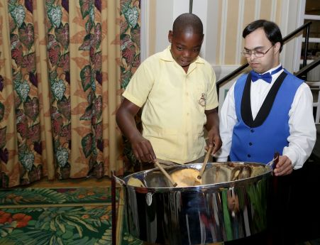 Pannist Fabian Pamphille of Lambeau Primary school plays the pan for visitor Sujeet Desai, the feature speaker at the conference.