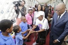 Darryl Julien, a pupil at the Montgomery Government Primary school, Rose's alma mata, holds the Victory Award while smiling up at Calypso Rose at the red carpet meet and greet as THA Chief Secretary Kelvin Charles looks on.