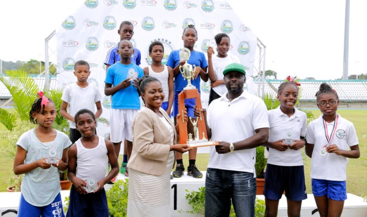 Assistant Secretary in the Office of the Chief Secretary Marisha Osmond presents Signal Hill Government School teacher Seldon Tobias with the trophy for the school who topped the 3K road race, while pupils of the school who took part in the event look on during the prize distribution ceremony at the Dwight Yorke Stadium.