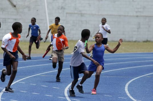 Signal Hill Primary's Tyrone Douglas, second from right, starts his run in the anchor leg for his team in the Boys U-9 4x100M event.