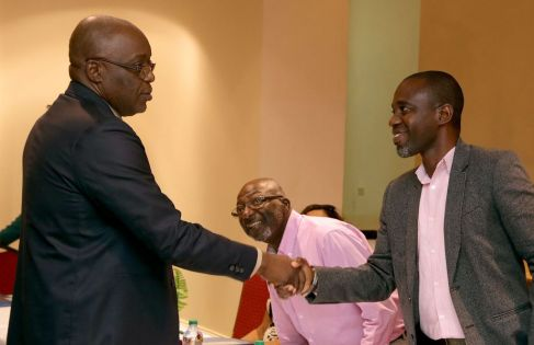 THA Chief Secretary Kelvin Charles greets incoming chairman of the Tobago Literacy Institute Lyndon Wilson, right, while outgoing chairman John Solomon, centre, looks on.
