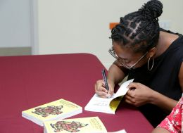 The author takes some time after the lecture to autograph copies of her book.