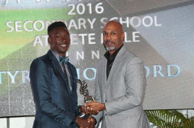 Secretary of Sport and Youth Affairs Jomo Pitt presents Tyriq Horsford with the award for Secondary School Male Athlete of the Year. Horsford also took the Male student of the Year category.
