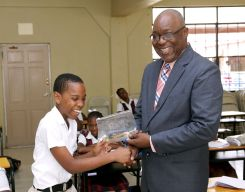 Isaiah Davidson cannot contain his smile during Chief Secretary Kelvin Charles' visit to Black Rock Government Primary School.