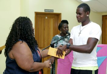 """Bmobile representative Onica Blackman presents Kerlon Sandy with the winner's prize for the C1 class race, won by """"My Way."""""""