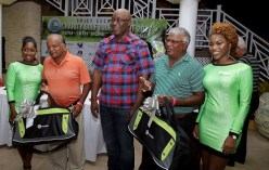 Second placed golfers Mani Seepersad and Sienanand Ragbir pose for a photo with THA Chief Secretary after collecting their prize for second place. Bmobile girls Leah Richards, left and Vanesha Johnson assisted in the prize distribution.