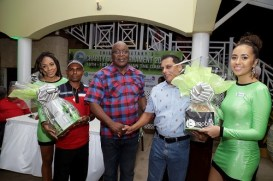 THA Chief Secretary Kelvin Charles congratulates Avin Ali, who won the bmobile round of golf on Friday with partner Omesh Dinanath. Bmobile girls Anolie Yeates, left and Bianca Garraway assisted in the prize distribution.
