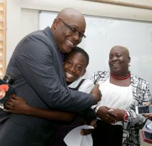 THA Chief Secretary Kelvin Charles embraces St Andrew's Anglican primary school pupil Kareah Manning, who placed third overall among pupils writing the SEA in Tobago. Looking on at right is Principal Nicole Henry.