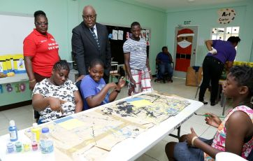 Chief Secretary Kelvin Charles chats with children attending the Happy Haven vacation camp during a visit to the school. With him at left is Principal Dianne Le Cointe.